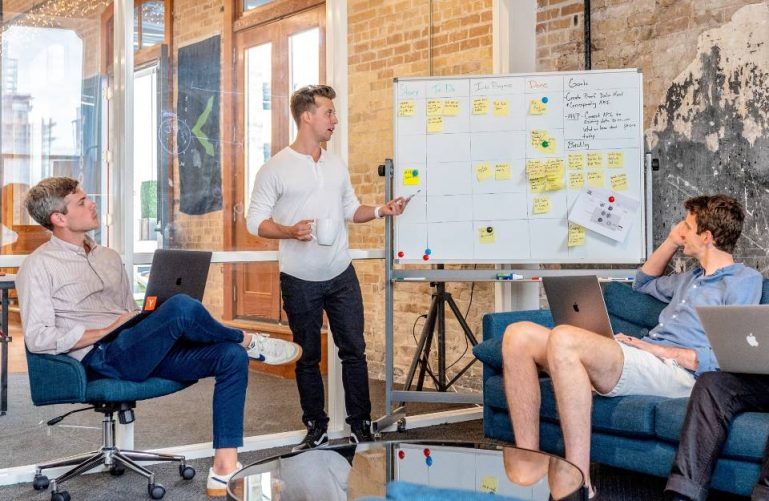 three men sitting in office discussing key performance indicators for their website